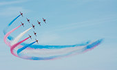 Vector illustration flat design of military jets with colored trails on blue background. Plane show illustration