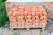 The red brick folded neatly on the foundation of the house. Home construction.