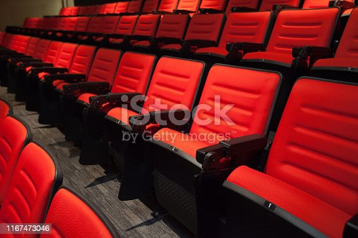 istock The red chairs without people in the cinema, Blurry background. 1167473046