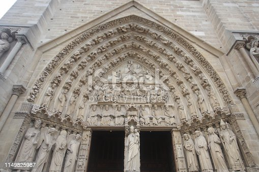 The Red Door of Gothic cathedral in West Portals Facade of Notre Dame, France, historic monuments detail ancient statue art outside of cathoric church, travel destination backgrounds