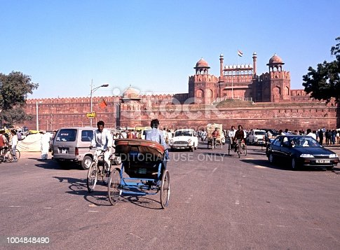 View of the Red Fort with local people on bicycles and rickshaws in the foreground, Delhi, Delhi Union Territory, India.