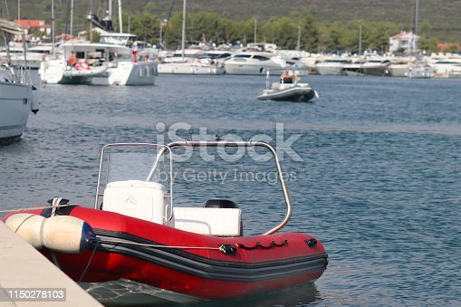 The red inflatable motor boat is moored to the pier in the background of the marina with yachts. Pilot ship to assist in the mooring of ships. Dingy staf. Infrastructure of the Mediterranean port.