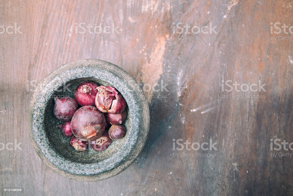 The red onion and stone mortar on old wooden. stock photo