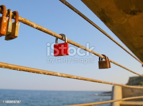 A red padlock hangs along a metal rope, along with rusted padlocks, set against the Mediterranean Sea in Rethymno, Crete.