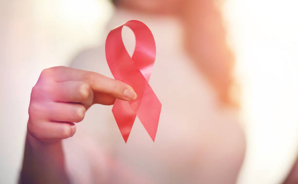 The red ribbon of the girl. The girl is holding a red ribbon. He The red ribbon of the girl. The girl is holding a red ribbon. Health concept red ribbon. Breast cancer. hiv stock pictures, royalty-free photos & images