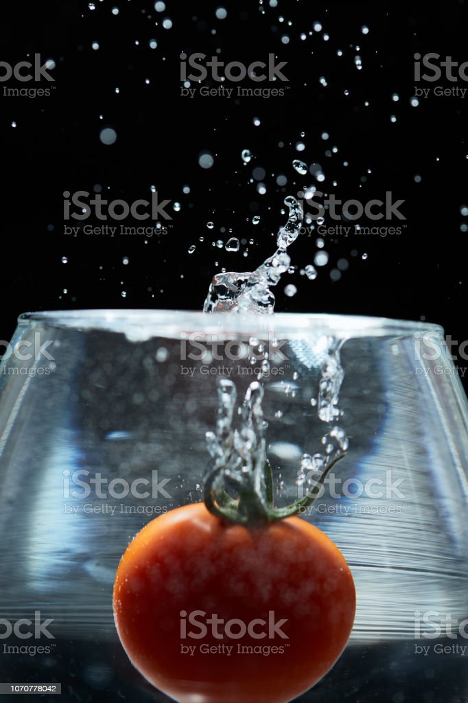 The red round mini tomato falls into the water of the glass and the...