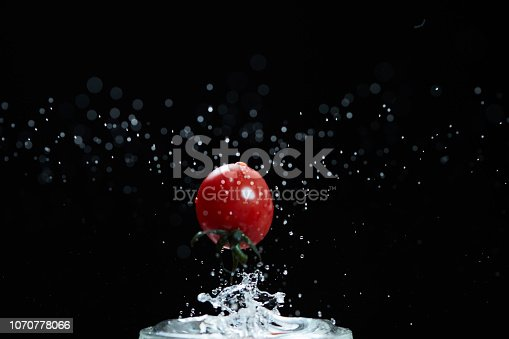 The red round mini tomato falls into the water of the glass and the splash of the splash is beautiful