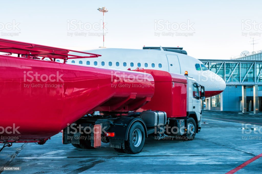 The red tanker refueling the aircraft parked to a boarding bridge at the airport apron стоковое фото