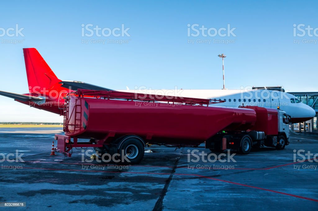 The red tanker refueling the plane parked to a boarding bridge at the airport apron stock photo