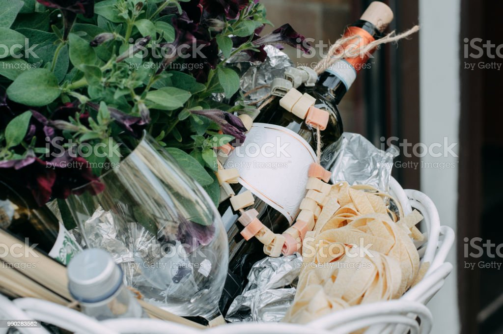The red wine unopened bottle, glass and blossom flowers in the white basket royalty-free stock photo