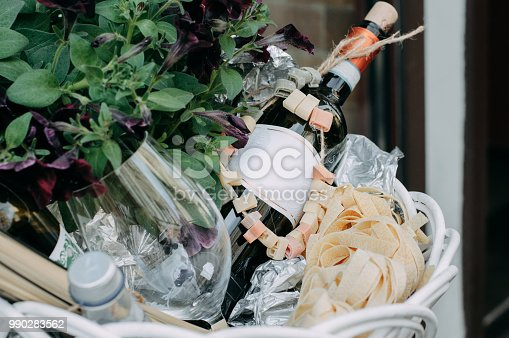 The red wine unopened bottle, glass and blossom flowers in the white basket