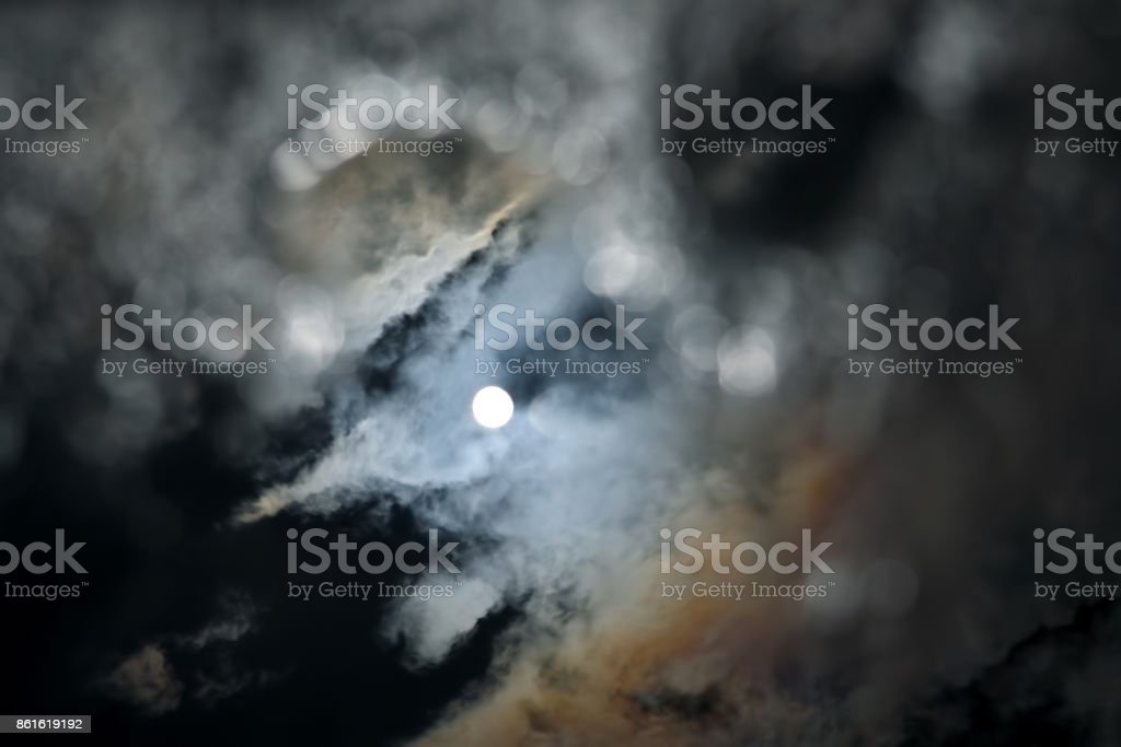 the reflection of the sun and clouds in a puddle of water stock photo