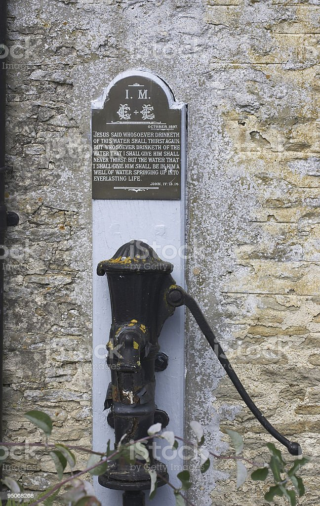 Cotswold village water pump with bible verse royalty-free stock photo
