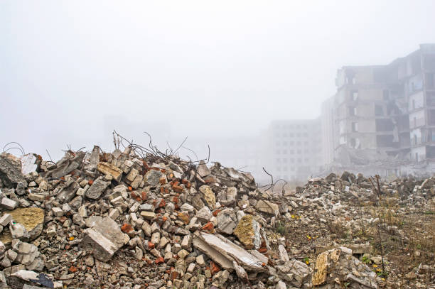 The remains of a large concrete building in the form of fragments of piles and piles of stones. The remains of the destroyed building in the form of piles and a blockage of a pile of stones on the background of a high destroyed structure in a foggy haze. The impact of the destruction. Background demolishing stock pictures, royalty-free photos & images