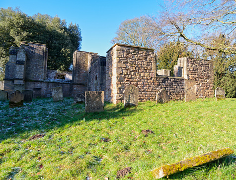 In the winter sun, amongst the trees,  stands the remains of a 13th century church with 17th and 18th century gravestones.