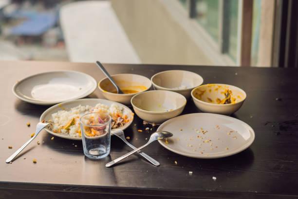 resterna av mat i tallrikar, smulor på bordet efter lunch eller middag - tallrik uppätet bildbanksfoton och bilder