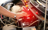 istock the repairman using the screw driver fixing the car battery in shop 871064950
