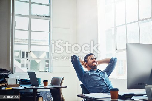 Shot of a young businessman relaxing at his work desk