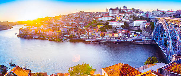 The Ribeira in Porto with a sunset and sunflare The Ribeira in Porto with a sunset and sunflare. Tourists take boat rides along the river Douro with many boats parked along the river banks. This is a popular tourist destination along the riverside with the Dom Luis I bridge on the right, a monument now declared a UNESCO World Heritage site. Porto is the second largest city of Portugal situated in the north of Portugal. duero stock pictures, royalty-free photos & images