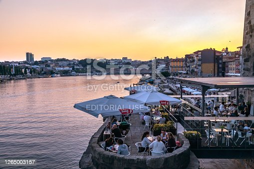 Ribeira or riverside in Porto with restaurants and tourists along the riverbank at sunset a popular tourist destination and one of UNESCO's World Heritage Sites.