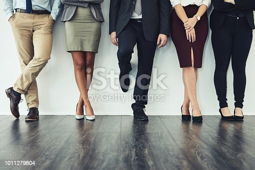 Cropped studio shot of a group of young businesspeople standing together in a row