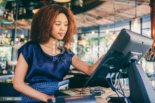 Cropped shot of a cashier looking at the computer monitor