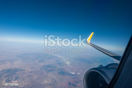 the right wing of the plane rises into the blue sky