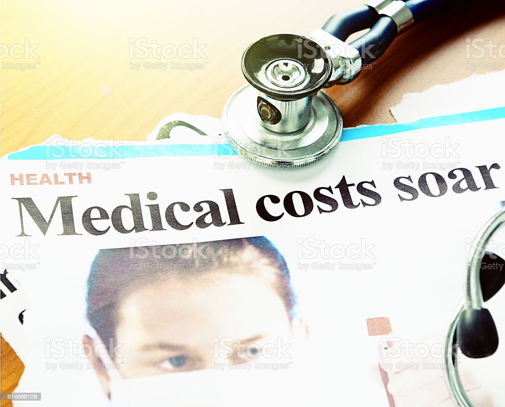 The rising price of healthcare: Newspaper article with stethoscope stock photo