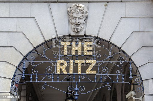 London, United Kingdom- May 16, 2013: The Ritz Hotel logo, illuminated with light bulbs and mounted on wrought iron work under the front arches of the Ritz building, Piccadilly, London, UK. The Ritz, opened in 1906, is a luxury hotel and international landmark in the west end of London.