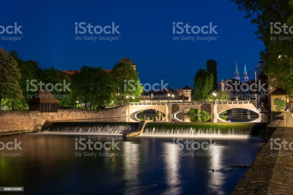 The river Pegnitz with cascades in the old town of Nuremberg, Germany during blue hour stock photo