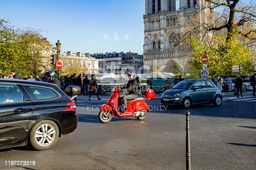 2019 The River Seine Pont St Louis in Paris with traffic and a red motor scooter in the foreground.