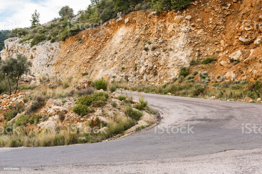 The road next to the towering hills stock photo