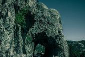 the road runs trough tunnel in the rock , Black hills , SD , USA