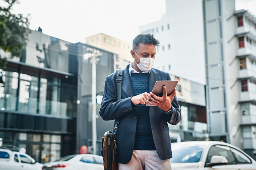 Shot of a masked businessman using a digital tablet against a city background