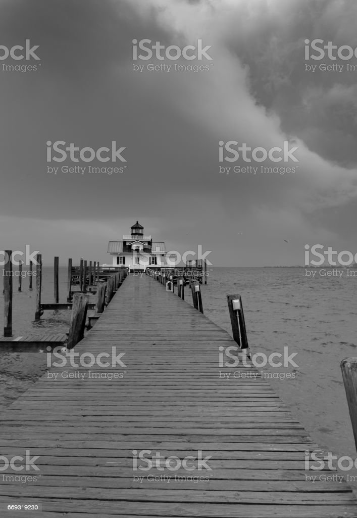 The Roanoke Island Lighthouse and wooden pier in a driving rain storm stock photo