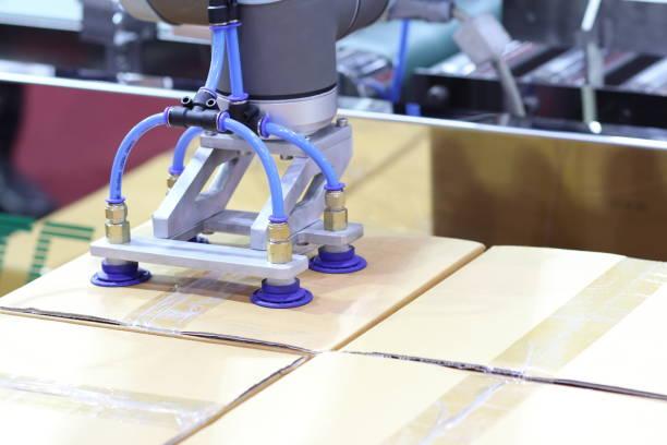 El brazo robótico transfiere la caja de cartón a la línea transportadora - foto de stock