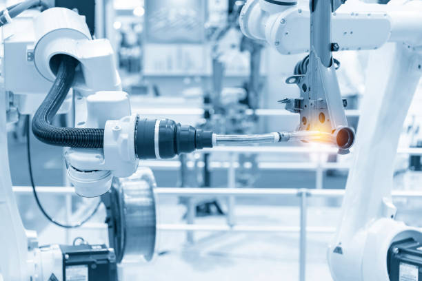 el brazo de robótica soldando las piezas automotrices. - robótica fotografías e imágenes de stock