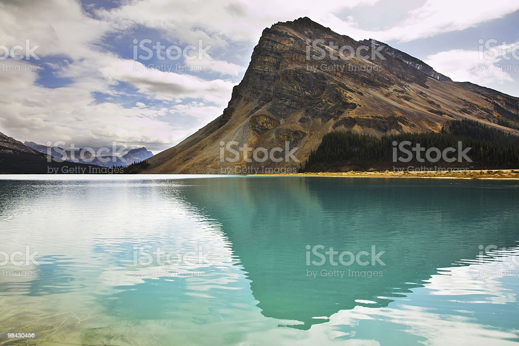 The  rock is reflected in emerald waters of  lake royalty-free stock photo
