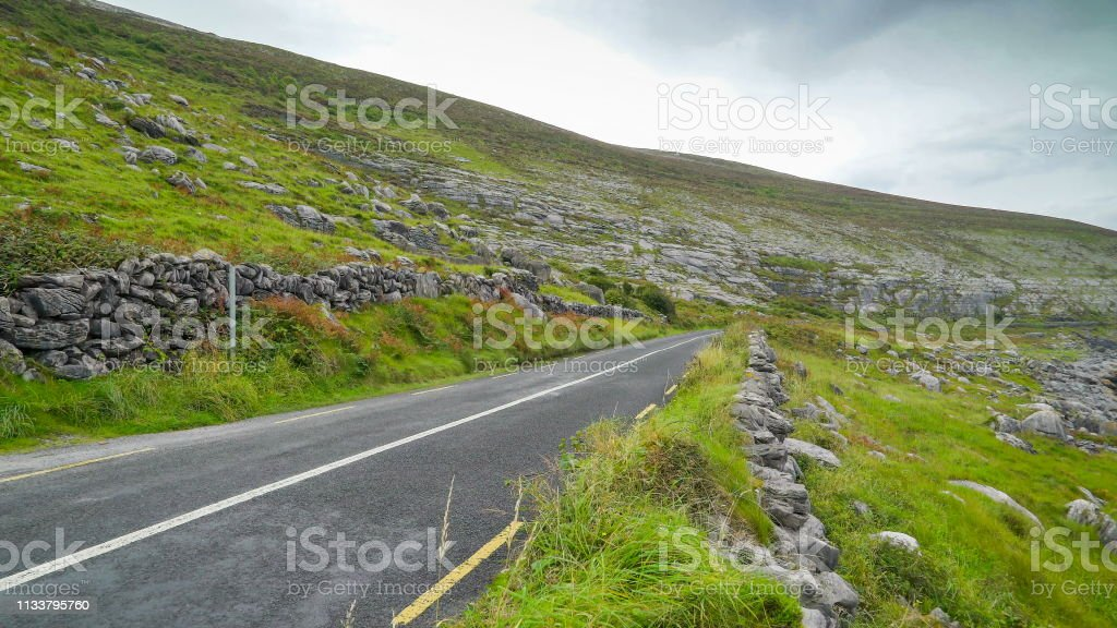 The rocks on the mountain in Ireland coast with the small road going...