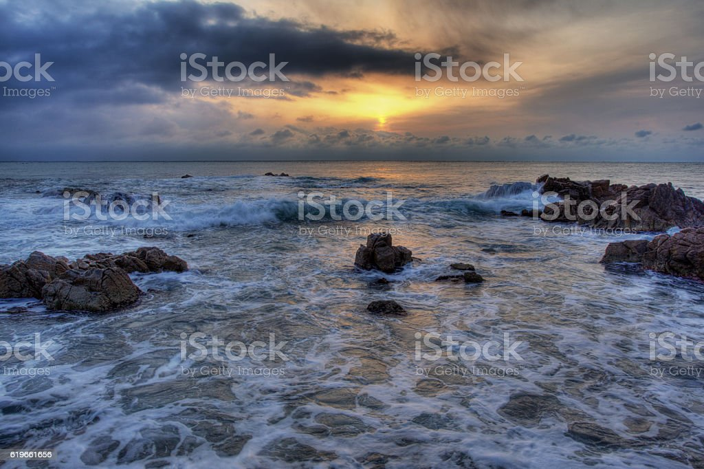 the rocks on the seashore at moody sunrise stock photo