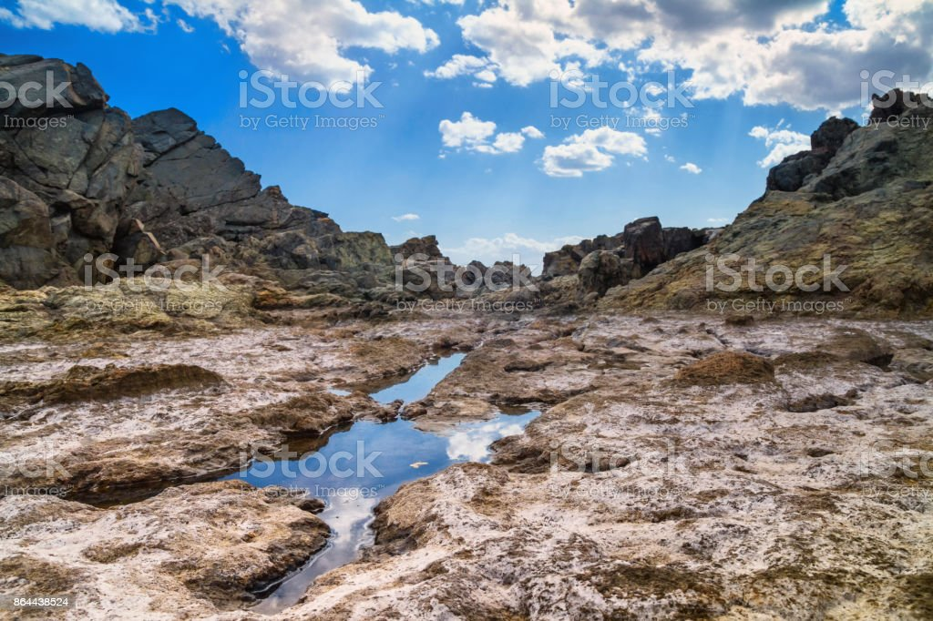 The rocky landscape under the sky with clouds stock photo