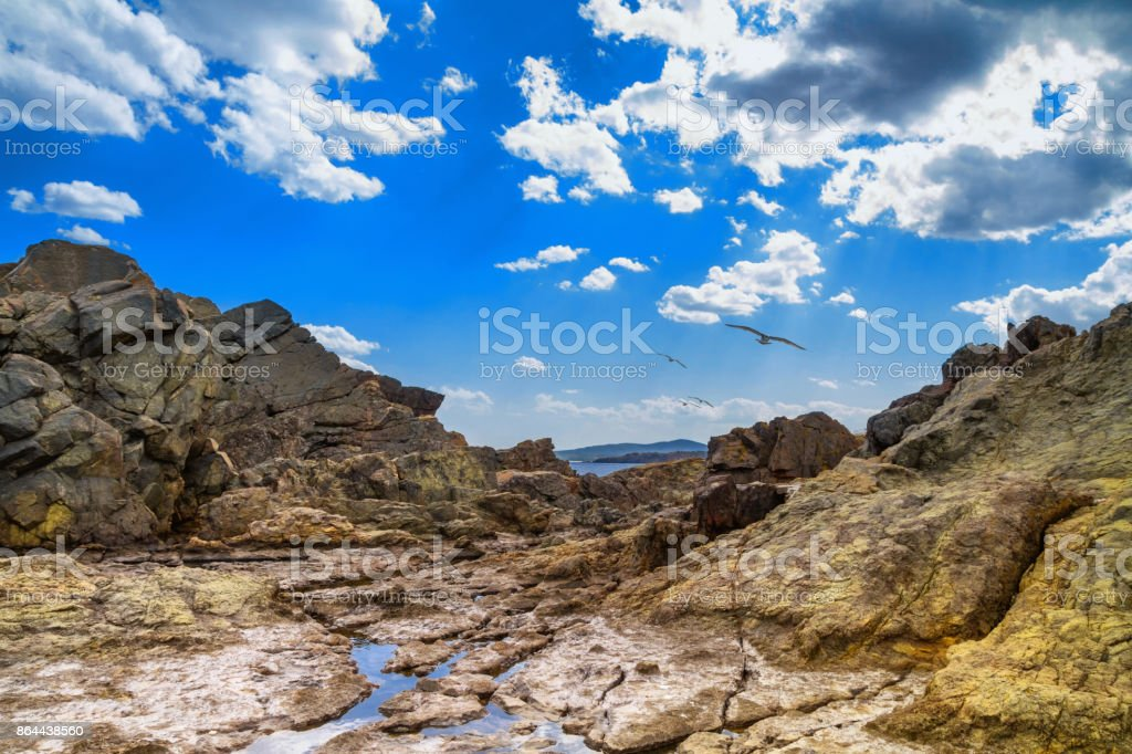 The rocky landscape with gulls under the sky with clouds stock photo