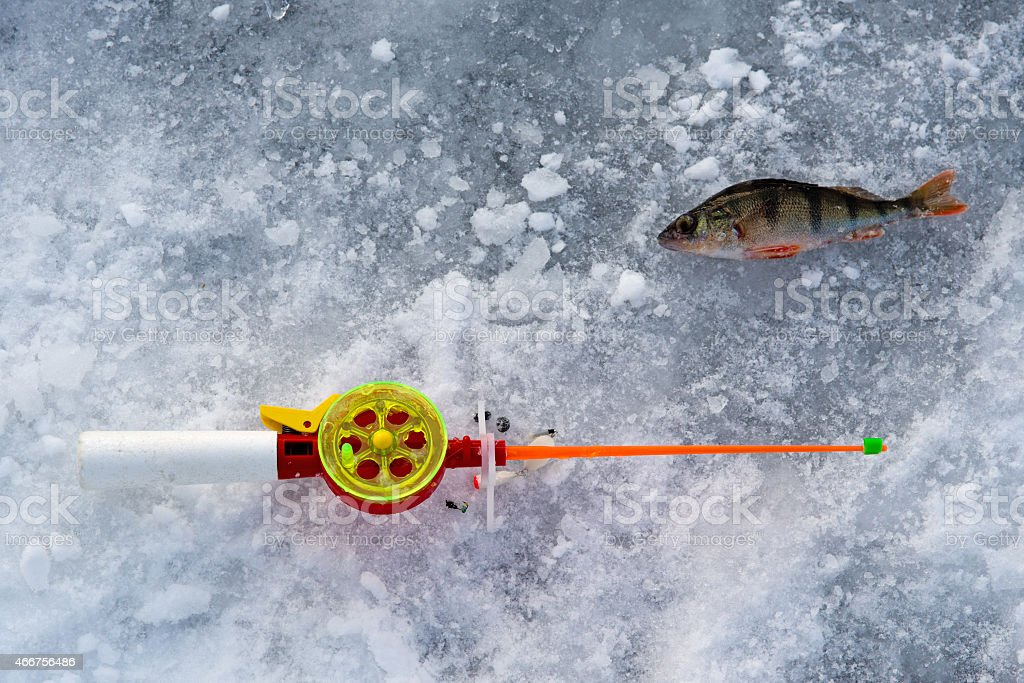 the rod for winter fishing lies near a hole stock photo