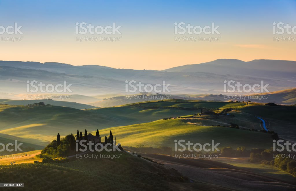 The rolling hills and green fields at sunrise, Tuscany, Italy stock photo