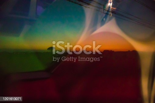 Intersection of colour from the train, with mixed shades of gold, green, yellow and red with degrees of transparency. Abstract