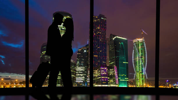 the romantic couple standing in the big hall with a beautiful night sky view - man look sky scraper foto e immagini stock