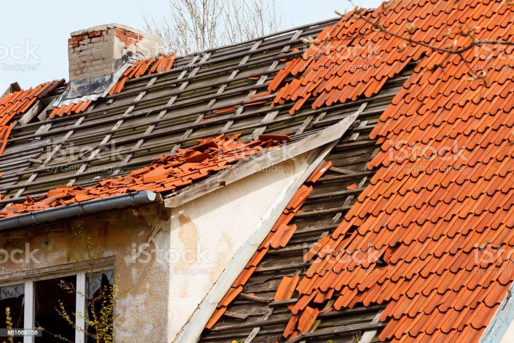 das Dach des alten Hauses mit einer beschädigten Beschichtung rote Keramik-Fliesen – Foto