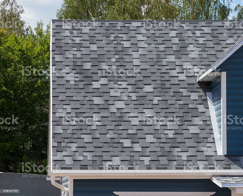 The roof with bitumen shingles stock photo