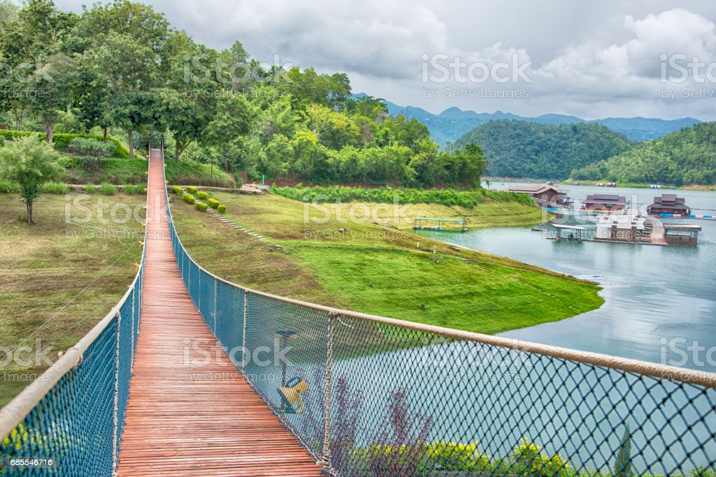 The rope bridge in the park directly onto the solitary island on the lake royalty-free 스톡 사진