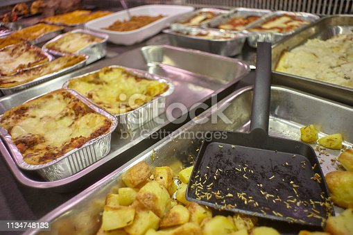 View of a refrigeration counter of a rotisserie full of cooked and ready to take away food